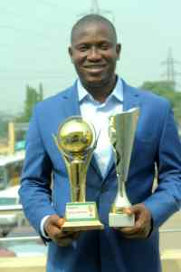 The Chairman of Odi Olowo/Ojuwoye LCDA posing with the two trophies won by the Club
