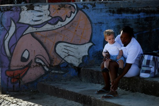 Maid tends to her employer's child on a beach in Rio de Janeiro