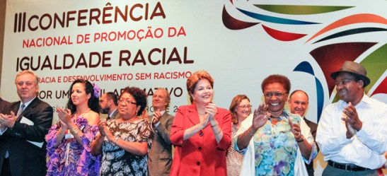 Participants in the CONAPIR conference included President Dilma Rouseff (in red) and minister of the Secretaria Especial de Políticas Públicas da Igualdade Racial (Secretariat of Public Policies for Racial Equality) – SEPPIR Luiza Bairros (women left and right of Rouseff)