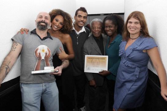 Writers João Ximenes Braga (far left) and Cláudia Lage (far right) pose with award and novela's cast Sheron Menezes, Marcelo Mello Jr., Milton Gonçalves and Zezé Barbosa