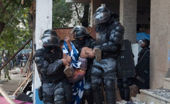 Child being removed from building by Military Police