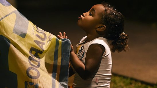 Young Marina Silva supporter waves the flag of the candidates' party (PSB) before a presidential debate
