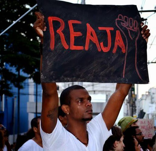 """Protester holds sign of the """"Reaja ou será mort@"""" (react or you will be killed) campaign"""