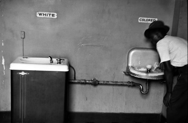 A fitting photo illustrates the issue: Water fountains for black and whites in era of legal segregation in the United States