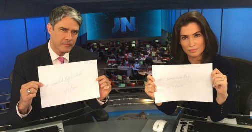 Anchors William Bonner and Renata Vasconcellos pose with posters with the phrase #SomosTodosMaju (We are all Maju) in 'support' of Coutinho who was the target of various racist comments online.