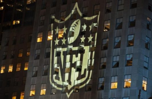 A man stands at a window lit by the NFL logo  in New York September 5, 2012. REUTERS/Lucas Jackson
