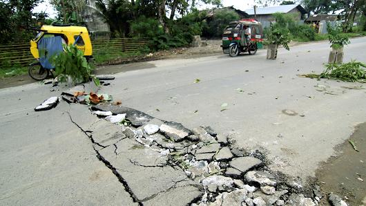 Vehicles pass cracks on a road that appeared along the National Highway at Rizal town after an earthquake hit Surigao city, southern Philippines February 11, 2017. (Reuters)