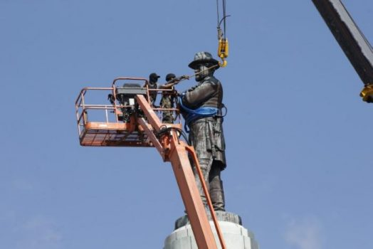 Construction workers attach a crane to a monument of Robert E. Lee, who was a general in the Confederate Army, before it is removed in New Orleans, Louisiana, U.S., May 19, 2017. REUTERS/Jonathan Bachman