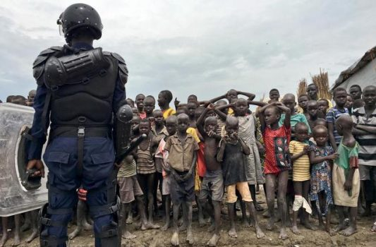 A crowd of displaced people look on as members of the U.N. multi-national police contingent provide security during a visit of UNCHR High Commissioner Filippo Grandi to South Sudan's largest camp for the internally-displaced, in Bentiu, South Sudan Sunday, June 18, 2017.  (AP Photo/Sam Mednick)