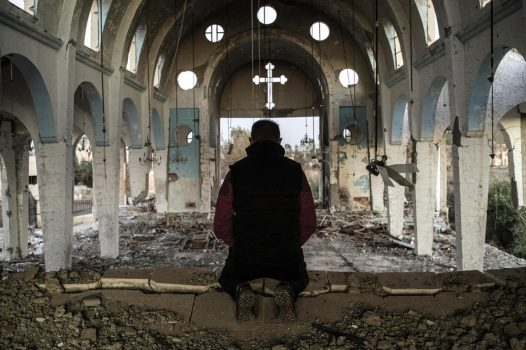 A resident of a village in the province of al-Hasake in the north-east of Syria prays on Dec. 8, 2015, in St. George's Church, which was destroyed by Islamic State terrorists. (Valeriy Melnikov, AP)