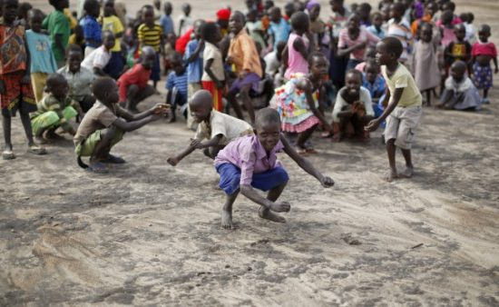 South Sudanese refugee children dance and sing before class on a dirt playing field at the Ombechi kindergarten in Uganda's Bidi Bidi refugee settlement. The overcrowded settlement is struggling to provide education to a steady stream of refugees. (Ben Curtis/AP)