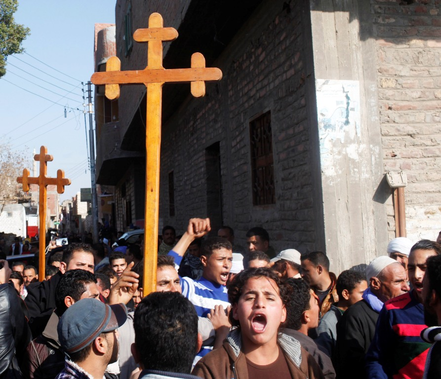 Relatives and neighbours of Egyptian Coptic men killed in Libya chant pro-army slogans during a protest while carrying crosses in al-Our village, in Minya governorate, south of Cairo February 16, 2015. Thousands of traumatized mourners gathered on Monday at the Coptic church in al-Our village south of Cairo, struggling to come to terms with the fate of compatriots who paid a gruesome price for simply seeking work in Libya. Thirteen of 21 Egyptians beheaded by Islamic State came from the impoverished dirt lanes of al-Our, violence that prompted the Egyptian military to launch an air strike on Islamic State militant targets in Libya.  REUTERS/Asmaa Waguih (EGYPT - Tags: POLITICS CIVIL UNREST RELIGION CONFLICT MILITARY)