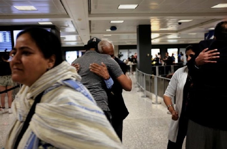 FILE PHOTO: International passengers embrace family members as they arrive at Washington Dulles International Airport after the Trump administration's travel ban was allowed back into effect pending further judicial review, in Dulles, Virginia, U.S., June 29, 2017. (REUTERS/James Lawler Duggan)