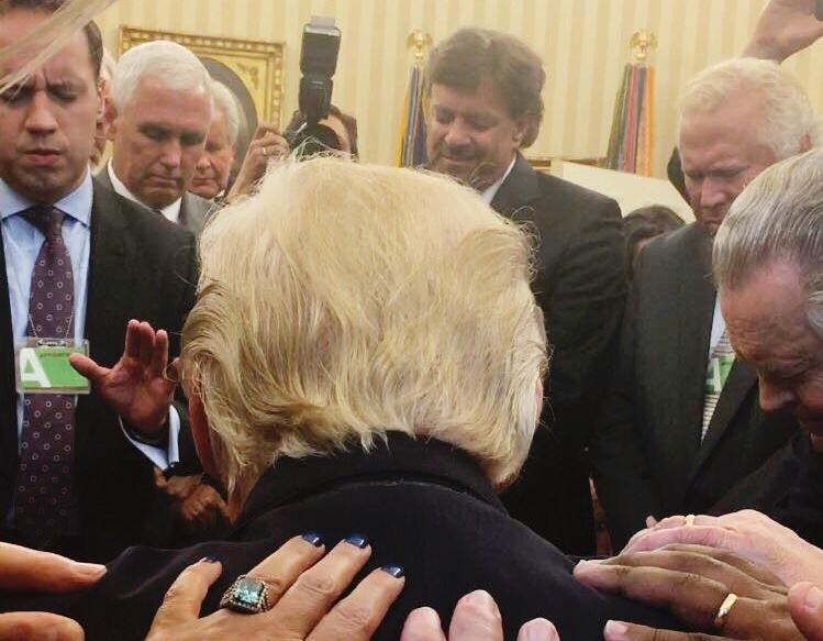 A group of evangelical leaders lay hands on President Donald Trump and pray over him at a White House Oval Office meeting on Monday, July 10, 2017. (Photo: Johnnie Moore)