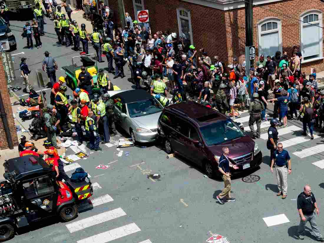 People receive first aid after a car ran into a crowd of protesters in Charlottesville, Va., on Saturday. The car struck the silver vehicle pictured, sending marchers into the air. (Paul J. Richards/AFP/Getty Images)
