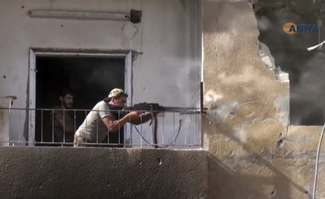 This video image released Aug. 3, 2017, by Hawar News Agency , a Syrian Kurdish activist-run media group, shows a fighter from the U.S.-backed Syrian Democratic Forces firing his weapon during clashes with Islamic State fighters in Raqqa, Syria. (HAWAR NEWS AGENCY/AP)