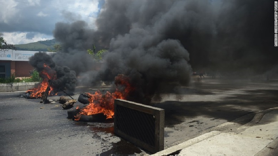 A barricade set by anti-government activists burns in flames in Valencia, Venezuela, on Sunday.