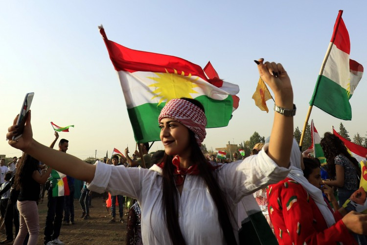 A Syrian Kurdish woman takes a selfie in the city of Qamishli on Tuesday during a gathering in support of the independence referendum in Iraq's semiautonomous Kurdish region. (Delil Souleiman/AFP/Getty Images)