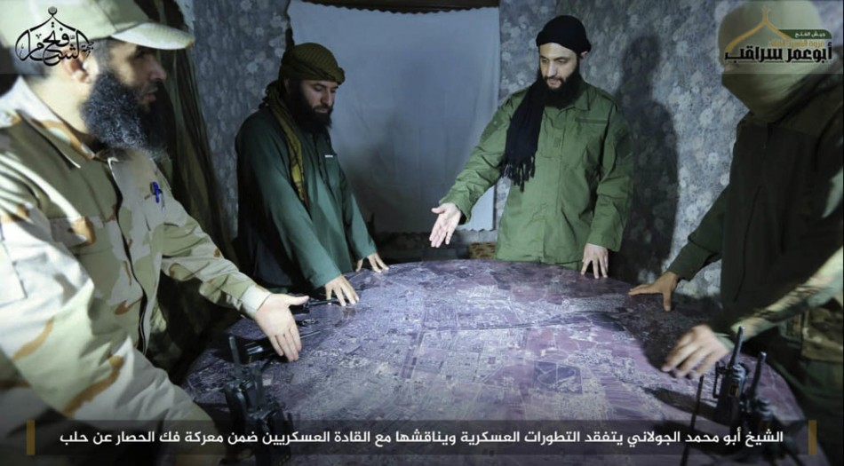 FILE -- This undated file photo, shows Abu Mohammed al-Golani, second right, then leader of Fatah al-Sham Front, in pictures posted by the group, discussing battlefield details with field commanders over a map, in Aleppo, Syria. (Associated Press)