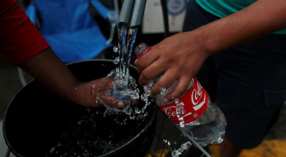 Local residents fill up plastic bottles during a water distribution in Bayamon following damages caused by Hurricane Maria. (REUTERS/Alvin Baez)