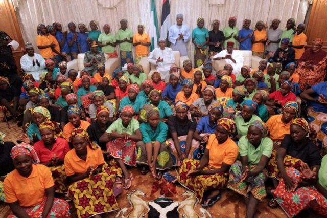 Nigeria's President Muhammadu Buhari (seated at center behind the girls) and other top Nigerian officials applaud as they welcome a group of Chibok girls, who were held captive for three years by the millitant group Boko Haram, in Abuja, Nigeria, on May 7, 2017. (PHOTO: BAYO OMOBORIOWO/PRESIDENTIAL OFFICE/HANDOUT VIA REUTERS)