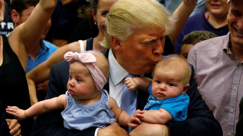 Republican presidential nominee Donald Trump kisses a baby at a campaign rally in Colorado Springs, Colorado in July 2016. (PHOTO: REUTERS/CARLO ALLEGRI)