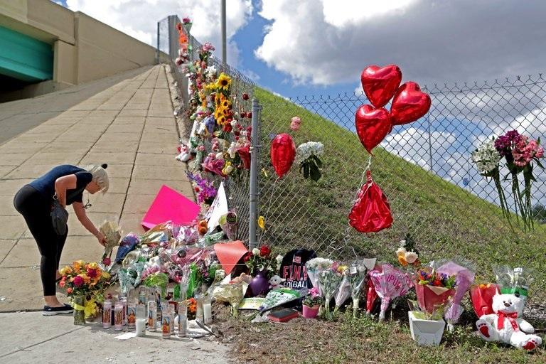 Ann Newman, of Deerfield Beach, Fla., a retired Broward County teacher, placed flowers at a memorial on Sunday at Marjory Stoneman Douglas High School in Parkland, Fla. (Credit: John McCall/South Florida Sun-Sentinel, via Associated Press)
