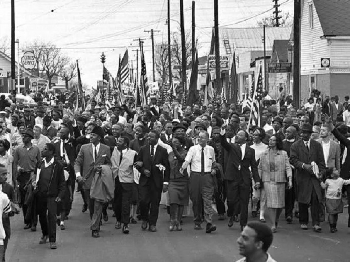 In this March 21, 1965, file photo, Dr. Martin Luther King, foreground row, fifth from right, waves as marchers stream across the Alabama River on the first of a five day, 50-mile march to the state capitol at Montgomery, Ala. (Photo: AP)