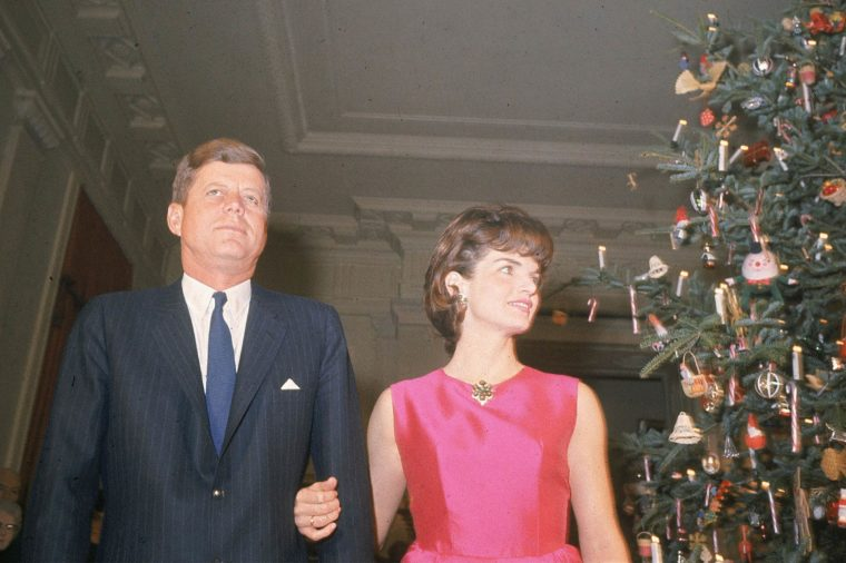 Jacqueline wraps her arm around John's as the Kennedys attend a 1962 holiday party in the White House.