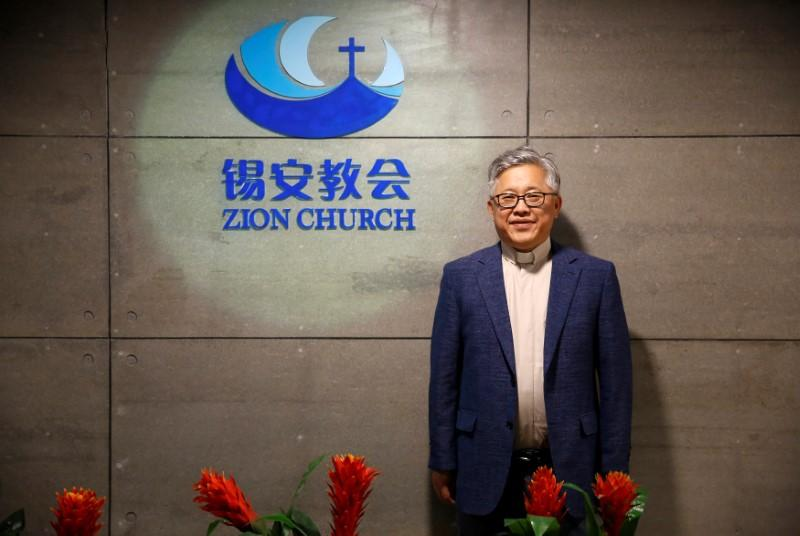 """The head pastor of the Zion church in Beijing Jin Mingri poses for picures in the lobby of the unofficial Protestant """"house"""" church in Beijing, China, August 28, 2018. (REUTERS/Thomas Peter)"""