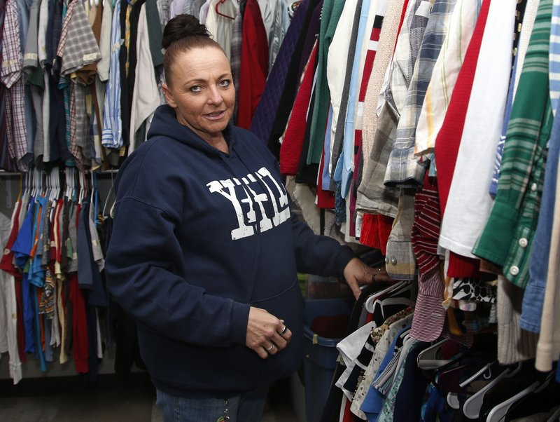Angel Nelson is pictured in the apparel closet at the Oklahoma City Day Shelter in Oklahoma City, Wednesday, Sept. 26, 2018. Nelson had three children when she did her first 18-month stint in an Oklahoma prison at age 24 for writing a bogus check. Nelson finished her most recent stint in March and now works two jobs. (AP Photo/Sue Ogrocki)