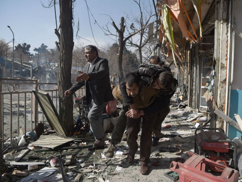 Afghan volunteers carry a body at the scene of a car bomb exploded in front of the old Ministry of Interior building in Kabul on January 27, 2018. An ambulance packed with explosives blew up in a crowded area of Kabul on January 27, killing at least 17 people and wounding 110 others, officials said, in an attack claimed by the Taliban. (WAKIL KOHSAR / AFP)