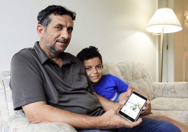 In this Sept. 29, 2018 photo, Hadi Mohammed sits with his 9 year old son Mohammed Ghaleb, as he displays a photo of his son as a baby in Baghdad, in their Lincoln, Neb. apartment. Death threats drove Hadi Mohammed out of Iraq and to a small apartment in Nebraska, where he and his two young sons managed to settle as refugees. But the danger hasn't been enough to allow his wife to join them. (AP Photo/Nati Harnik)