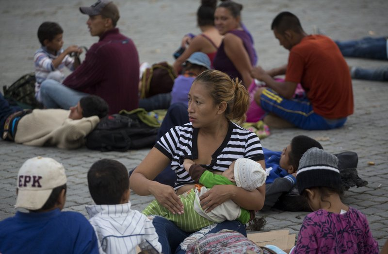 A Honduran migrant breastfeeds her daughter before starting to walk again as part of a caravan of hundreds of Honduran migrants making their way the U.S. in Esquipulas, Guatemala, early Tuesday, Oct. 16, 2018. U.S. President Donald Trump threatened on Tuesday to cut aid to Honduras if it doesn't stop the impromptu caravan of migrants, but it remains unclear if governments in the region can summon the political will to physically halt the determined border-crossers. (AP Photo/Moises Castillo)