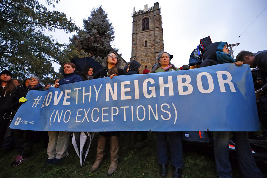 A group holds a sign at the intersection of Murray Ave. and Forbes Ave. in the Squirrel Hill section of Pittsburgh, during a memorial vigil for the victims of the shooting at the Tree of Life Synagogue where a shooter opened fire, killing multiple people and wounding others, including several police officers, Saturday, Oct. 27, 2018. (AP Photo/Gene J. Puskar)
