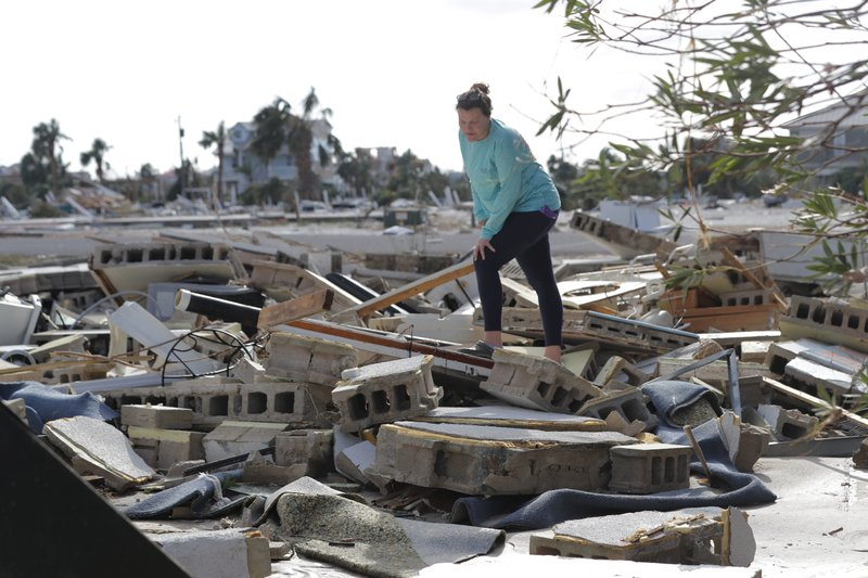 FILE- In this Oct. 11, 2018 file photo, Mishelle McPherson looks for her friend Agnes Vicari in the rubble of her home in Mexico Beach, Fla. Vicari stayed in her home during Hurricane Michael and has not been found. The storm that ravaged the Panhandle left incredible destruction, but so far getting a firm grasp on how many died is proving somewhat elusive. (AP Photo/Gerald Herbert, File)