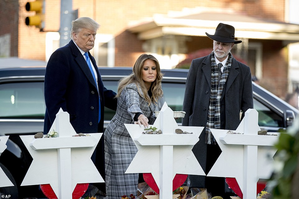 President Donald Trump and first lady Melania Trump placed stones and white flowers Tuesday on memorials to 11 members of the Tree of Life Synagogue who a Pittsburgh gunman mowed down on Saturday; Rabbi Jeffrey Myers accompanied them.