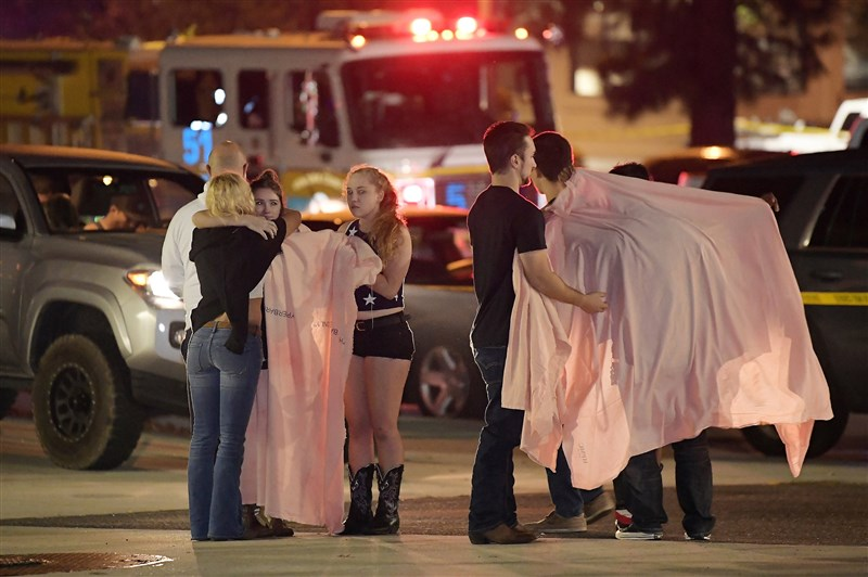 People comfort each other near the scene of Wednesday's mass shooting in Thousand Oaks, California. (Mark J. Terrill / AP)