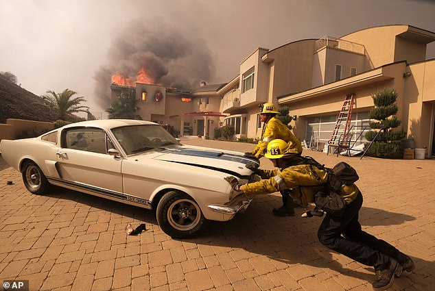 More than 170 people have filed a lawsuit against Southern California Edison (SCE) for allegedly starting the Woolsey Fire in California. Among those suing are Gary and Diane Cerveny, who lost their entire collection of 71 rare cars and motorbikes appraised at $8 million. Pictured: Firefighters trying to save a vintage car at the Cervenys' home.