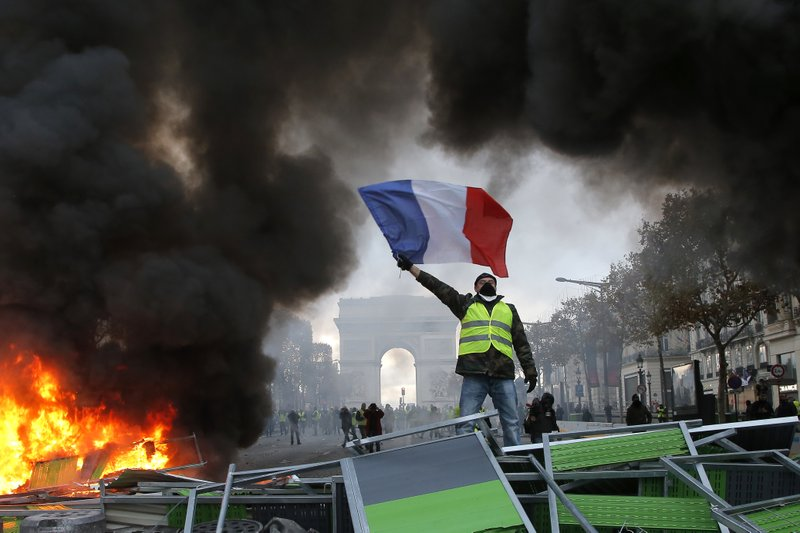 FILE - In this Nov. 24, 2018 file photo, a demonstrator waves the French flag on a burning barricade on the Champs-Elysees avenue with the Arc de Triomphe in background, during a demonstration against the rise of fuel taxes. Across the world, people are questioning truths they had long held to be self-evident, and they are dismissing some of them as fake news. They are replacing traditions they had long seen as immutable with haphazard reinvention. In France, people who feel left behind by a globalizing world have spent the last few weeks marching and rioting to protest a government they call elitist and out of touch. (AP Photo/Michel Euler, File)