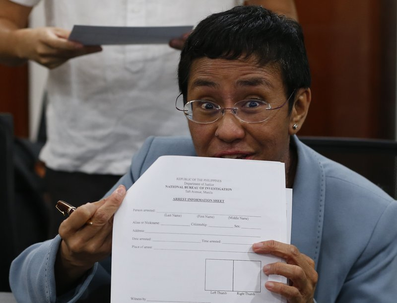 """Maria Ressa, the award-winning head of a Philippine online news site Rappler that has aggressively covered President Rodrigo Duterte's policies, shows an arrest form after being arrested by National Bureau of Investigation agents in a libel case Wednesday, Feb. 13, 2019 in Manila, Philippines. Ressa, who was selected by Time magazine as one of its Persons of the Year last year, was arrested over a libel complaint from a businessman which Amnesty International has condemned as """"brazenly politically motivated."""" Duterte's government says the arrest was a normal step in response to the complaint. (AP Photo/Bullit Marquez)"""