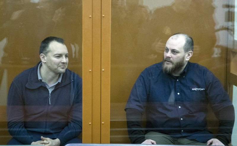 The former chief of the cybercrime department at Russia's main domestic security agency Sergei Mikhailov, left, and the former employee of Kaspersky Lab cybersecurity firm Ruslan Stoyanov attend a hearing in a court in Moscow, Russia, Tuesday, Feb. 26, 2019. Moscow's District Military Court stripped Sergei Mikhailov of his colonel's rank and ordered him to pay a 400,000-ruble ($6,130) fine and handed a 14-year sentence to Ruslan Stoyanov who was charged in the same case. (AP Photo/Pavel Golovkin)