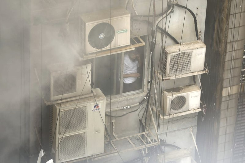 A Bangladeshi, stuck in a multi-storied office building on fire, speaks on his mobile phone in Dhaka, Bangladesh, Thursday, March 28, 2019. Fire Department control room official Ershad Hossain said by phone the FR Tower in Dhaka's Banani commercial district caught fire Thursday afternoon and at least 19 fire fighting units joined the operation to douse the blaze and rescue the people trapped inside. (AP Photo/Mahmud Hossain Opu)