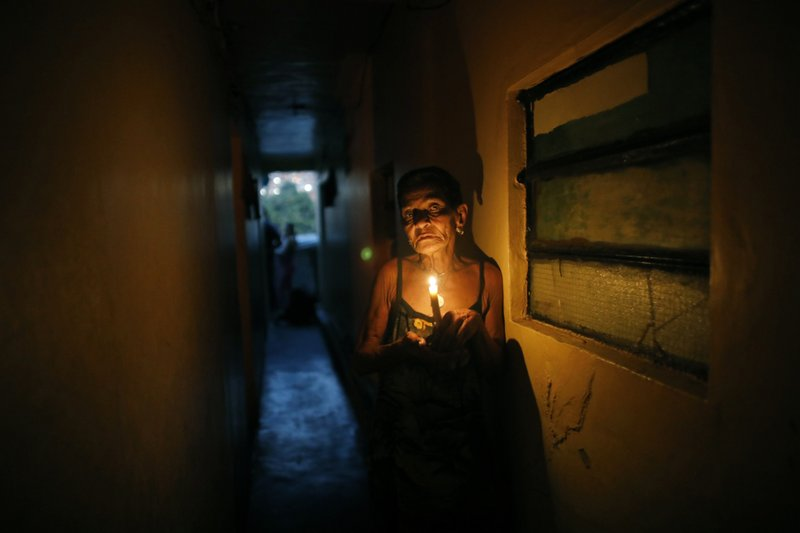 "72-year-old Elizabeth Guzman Espitia navigates a narrow passages up to her windowless room she calls her ""little cave"" during a blackout in the Santa Cruz of the East neighborhood, in Caracas, Venezuela, Thursday, March 14, 2019. I've never see a crisis like this. It's the first time,"" Espitia said. ""It makes me so sad."" Venezuela's power grid crashed March 7, throwing almost all of the oil-rich nation's 30 million residents into chaos for nearly a week. (AP Photo/Ariana Cubillos)"