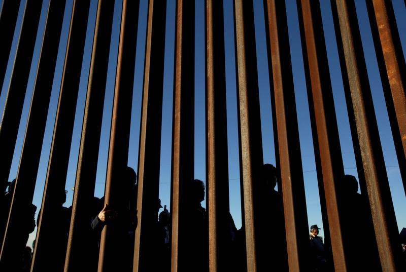 FILE PHOTO: People gather on the U.S. side of the border fence between Mexico and the United States during an inter-religious service against U.S. President Donald Trump's border wall, in Ciudad Juarez, Mexico February 26, 2019. REUTERS/Jose Luis Gonzalez -/File Photo