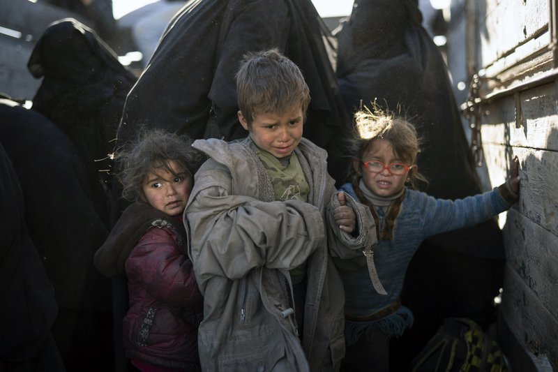 Women and children exit the back of a truck as they arrive to a U.S.-backed Syrian Democratic Forces (SDF) screening area after being evacuated out of the last territory held by Islamic State militants, in the desert outside Baghouz, Syria, Friday, March 1, 2019. (AP Photo/Felipe Dana)