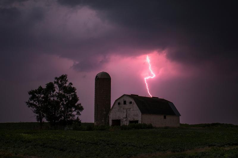 FILE PHOTO: Lighting strikes over a barn surrounded by a soybean crop in Donnellson, Iowa, July 13, 2012. REUTERS/Adrees Latif/File Photo