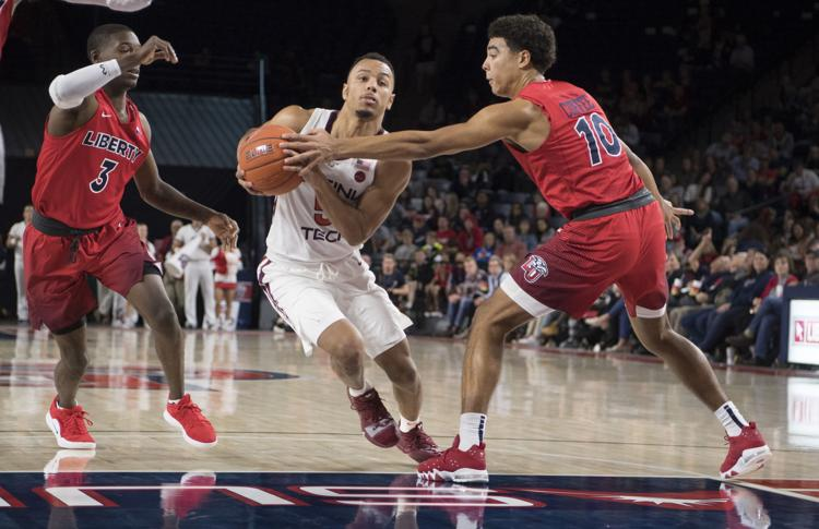 Virginia Tech guard Justin Robinson (center) took on the likes of Liberty's Lovell Cabbil (left) and Elijah Cuffee when the Hokies and Flames faced off in a benefit exhibition game back in November. (Associated Press)