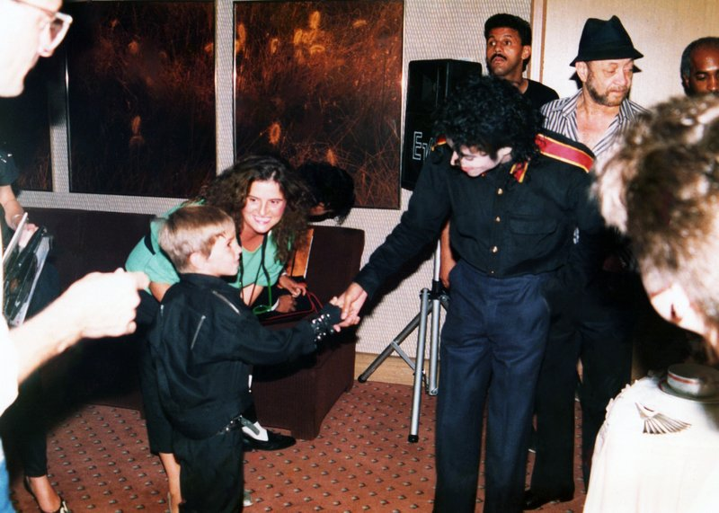 """This image released by HBO shows a young Wade Robson shaking hands with pop icon Michael Jackson in 1987, in a scene from the documentary """"Leaving Neverland."""" A trio of high-profile child sexual abuse documentaries have generated intense scrutiny of parents. But what critics with no experience of their own may not realize, experts say, is parents of young victims can be groomed by perpetrators along with their children. (Dan Reed/HBO via AP)"""