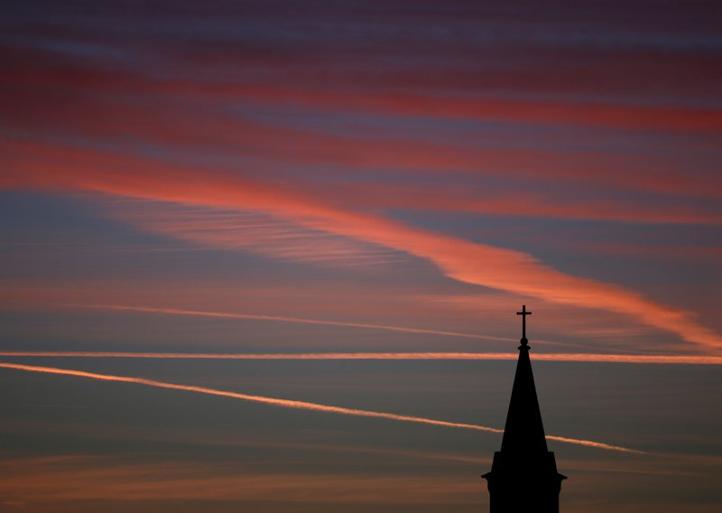 FILE - In this Saturday, Jan. 18, 2014 file photo, contrails from jets glow pink as they are illuminated by the setting sun in the skies beyond a church in Kansas. According to a Gallup poll released on Thursday, April 18, 2019, the percentage of U.S. adults who belong to a church or other religious institution has plunged by 20 percentage points over the past two decades, hitting a low of 50% last year. (AP Photo/Charlie Riedel)